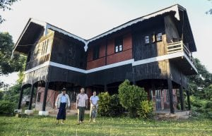 In this Nov. 14, 2016 photo, amateur George Orwell scholar Nyo Ko Naing, center, leaves the house of the former British commissioner in Katha with the caretaker, right, and Kyal Ni, member of the local office of the National League for Democracy, in Katha, Myanmar. Many of the places depicted in George Orwell's novel 'Burmese Days' remain standing in a sleepy Myanmar town, nearly 90 years after he left it. Now residents of Katha are working to make the most of that heritage, including by renovating a historic house to be a museum. (AP Photo/Aung Naing Soe)